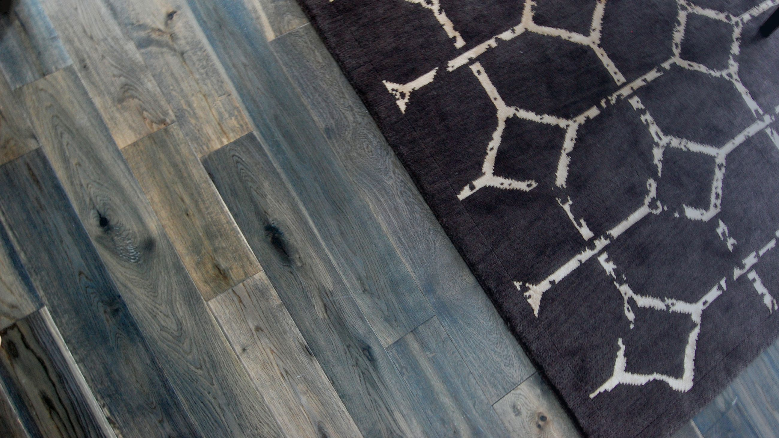 Hand-scraped multi-color wood flooring with geometric brown area rug.